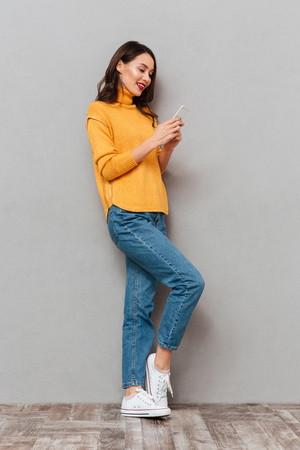 Full length image of Pleased brunette woman in sweater writing message on smartphone over gray background Foto de archivo