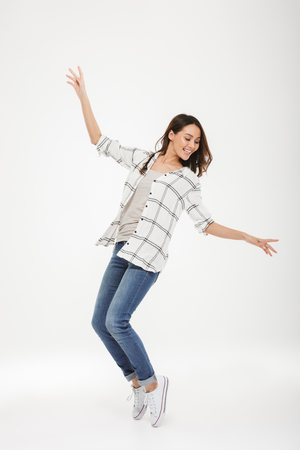 Full length image of Cheerful brunette woman in shirt dancing over gray background Stock Photo