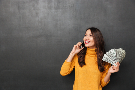 Smiling brunette woman in sweater holding money and talking by smartphone while looking away over black background
