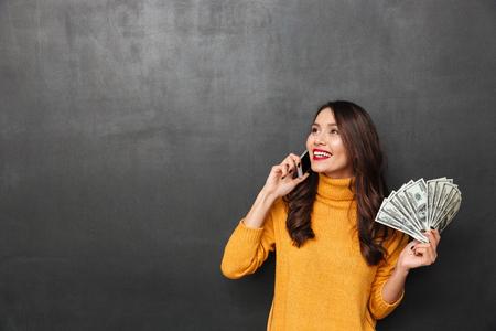 Mujer morena sonriente en suéter sosteniendo el dinero y hablando por teléfono inteligente mientras mira lejos sobre fondo negro Foto de archivo - 95018998