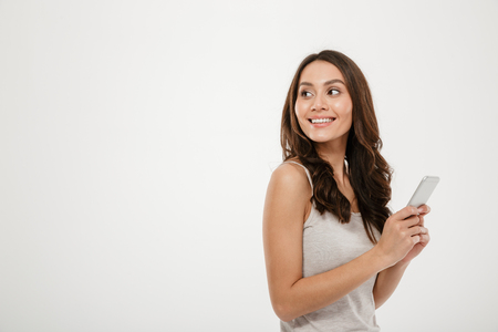 Side view of happy brunette woman holding smartphone and looking back over gray background