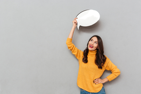 Happy brunette woman in sweater with arm on hip holding blank speech bubble overhead and looking up over gray background