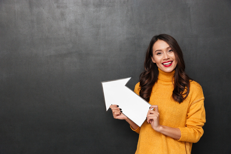 Smiling brunette woman in sweater pointing with paper arrow away and looking at the camera over black background Banque d'images