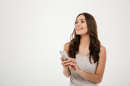 Smiling brunette woman holding smartphone and looking away over gray background
