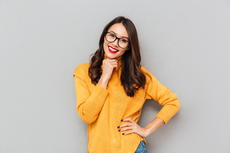 Happy brunette woman in sweater and eyeglasses with arm on hip looking at the camera over gray background