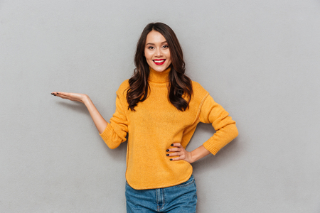 Pleased brunette woman in sweater with arm on hip holding copyspace on the palm and looking at the camera over gray background