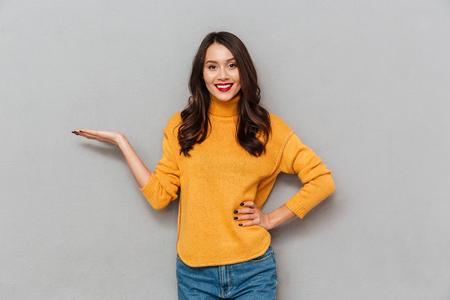 mujer morena satisfecho en suéter con el brazo en la cadera que sostiene el copyspace en la palma y mirando a la cámara sobre fondo gris