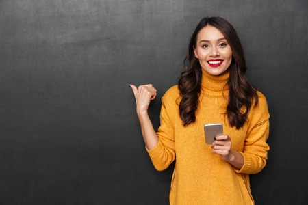 Smiling brunette woman in sweater holding smartphone and pointing on copyspace while looking at the camera over black background Standard-Bild