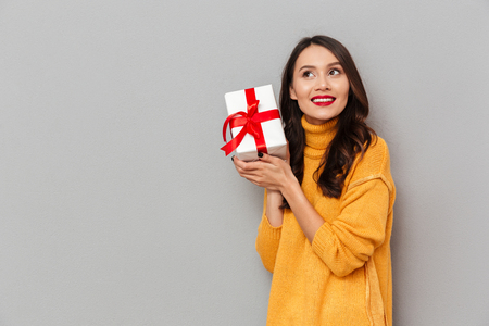 Smiling intrigued brunette woman in sweater holding gift box and looking away over gray background