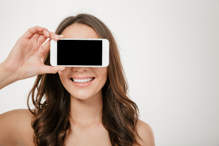 Smiling brunette woman covering her eyes and showing blank smartphone screen over gray background Stock Photo