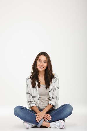 Vertical image of Smiling brunette woman in shirt sitting on the floor and looking at the camera over gray background Stock Photo