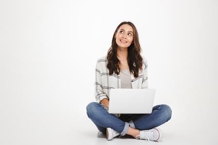 Zamyślony uśmiechnięta brunetka kobieta w koszuli siedzi na podłodze z laptopem i patrząc na szarym tle