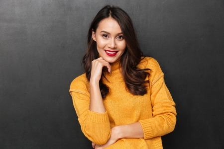 Pleased brunette woman in sweater posing and looking at the camera over black background Stock Photo