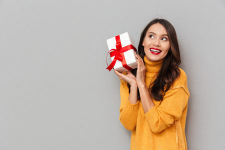 Pleased brunette woman in sweater holding gift box and looking away over gray background Foto de archivo