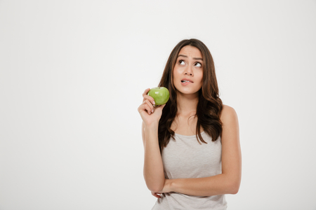 Portrait of puzzled woman looking upward holding green fresh apple thinking about healthy food isolated over white background Imagens - 95019620