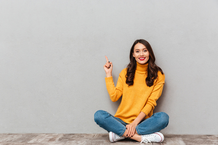 Smiling brunette woman in sweater sitting on the floor and pointing at copyspace while looking at the camera over gray background Standard-Bild