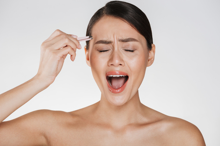 Beauty image of stressed young woman with brown hair screaming in pain while plucking eyebrows using tweezers isolated over white background