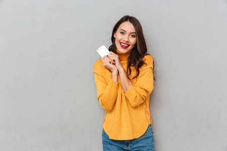 Pleased brunette woman in sweater holding smartphone and looking at the camera over gray background