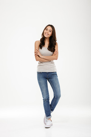 Full length image of Happy brunette woman posing with crossed arms and looking at the camera over gray background