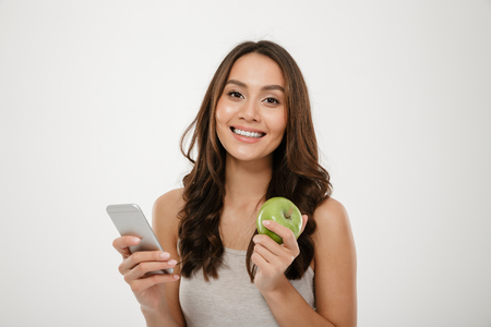 Portrait of satisfied woman with perfect smile using silver smartphone and eating fresh green apple isolated over white wall