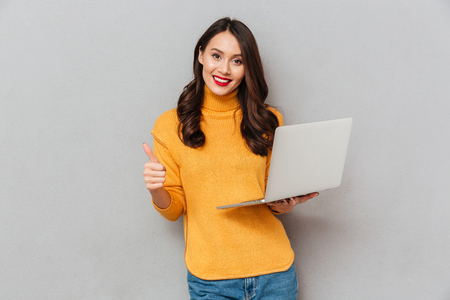 Happy brunette woman in sweater holding laptop computer and showing thumb up while looking at the camera over gray background