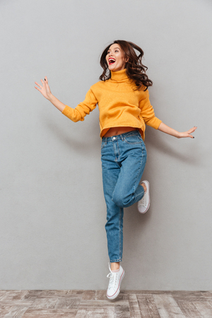 Full length image of Happy brunette woman in sweater jumping and looking away over gray background Foto de archivo