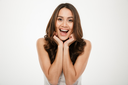 Picture of Joyful brunette woman posing and looking at the camera over gray background