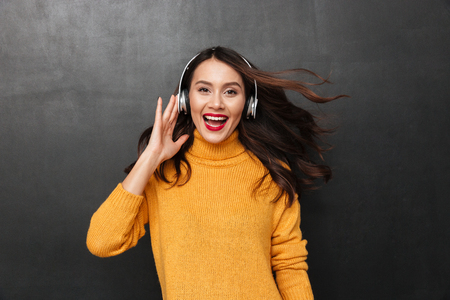 Happy brunette woman in sweater and headphones listening music while looking at the camera over black background