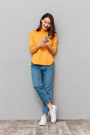 Full length image of Happy brunette woman in sweater writing message on smartphone over gray background Stock Photo