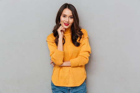 Smiling brunette woman in sweater posing and looking at the camera over gray background Stock Photo