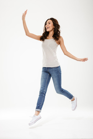 Full length image of Pleased brunette woman jumping and waving away over gray background Imagens