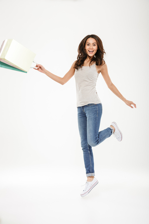 Full-length picture of delighted adult girl levitating or jumping with lots of colorful shopping bags in hand isolated over white background Banco de Imagens