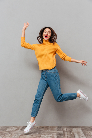 Full length image of Surprised happy brunette woman in sweater jumping and looking at the camera over gray background
