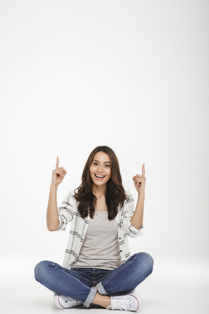 Full-length portrait of pleased woman in casual clothes sitting in lotus pose on the floor and pointing index fingers up isolated over white wall