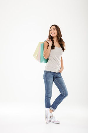 Full-length picture of fancy adult girl looking away and holding colorful shopping bags isolated over white background