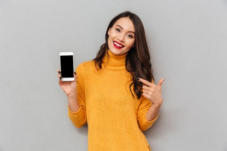 Smiling brunette woman in sweater showing blank smartphone screen and pointing on it while looking at the camera over gray background