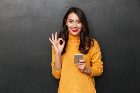 Smiling brunette woman in sweater holding smartphone and showing ok sign while looking at the camera over black background