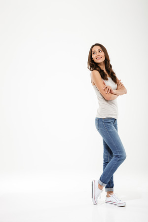 Full length image of Pleased brunette woman posing sideways with crossed arms looking back over gray background