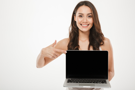 Horizontal photo of happy woman 30s smiling and demonstrating black empty screen of silver laptop on camera with finger over white wall Reklamní fotografie