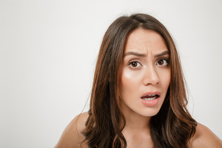 Close up portrait of confused caucasian woman looking on camera in puzzlement with facial expressions isolated over white background Stock Photo