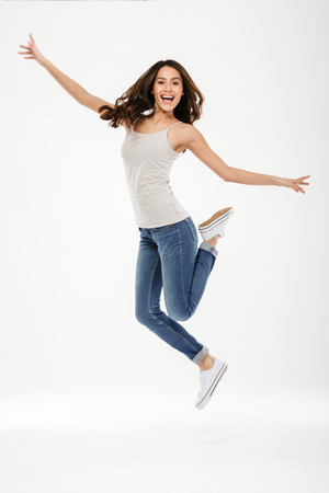 Full length image of Happy brunette woman jumping and rejoices while looking at the camera over gray background