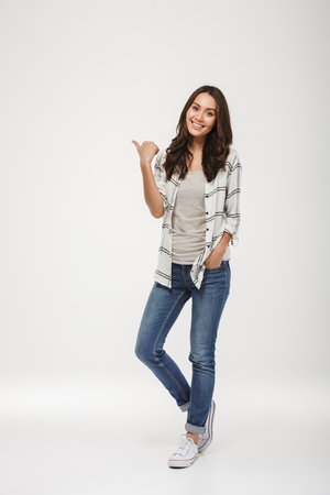 Full length image of Smiling brunette woman in shirt pointing away and looking at the camera over gray background