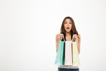 Horizontal picture of surprised woman posing on camera with open mouth and holding lot of shopping packs isolated over white wall copy space
