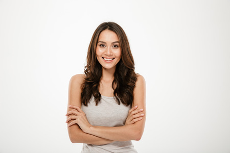 Smiling brunette woman with crossed arms looking at the camera over gray background