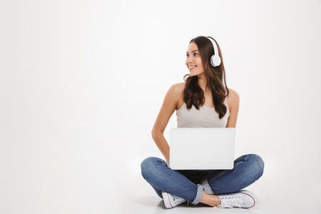 Photo of pretty woman listening to music or chatting using headphones and laptop while sitting with legs crossed on the floor over white wall Stock Photo