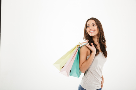 Horizontal picture of trendy woman posing on camera with shopping packs in hand isolated over white wall copy space