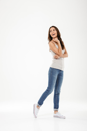 Full length image of Happy brunette woman posing and looking back over gray background