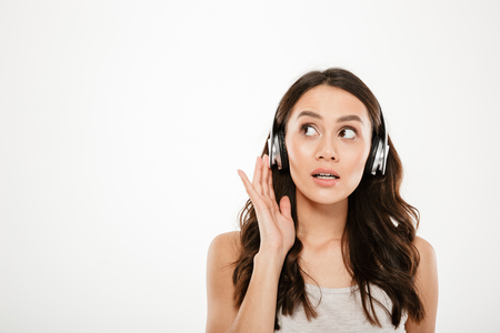 Mystery brunette woman in headphones listening music and looking away over gray background Stock Photo