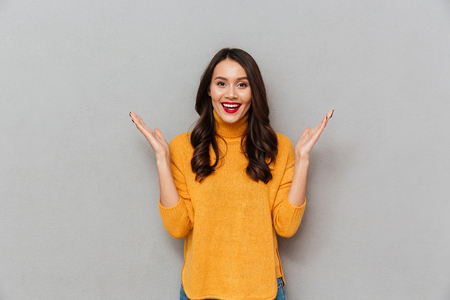 Surprised pleased brunette woman in sweater looking at the camera over gray background Stock Photo