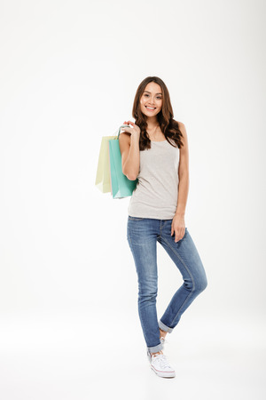 Full-length picture of fashion pretty woman holding packages with goods after shopping and looking on camera isolated over white wall Banco de Imagens
